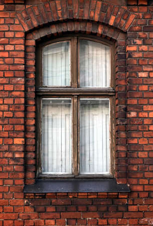 Tightly closed vintage vertical wooden window in red brick wall as fragment of old living house front view closeup Imagens