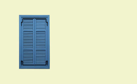 Front view of neat blue window with closed striped shutters on beige stucco wall close up with free space for text at right