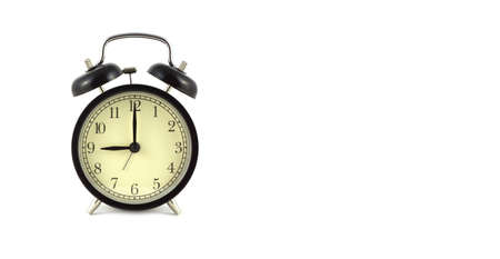 Alarm clock in black case shows 9 oclock isolated on white background front view close up with free space for text at right