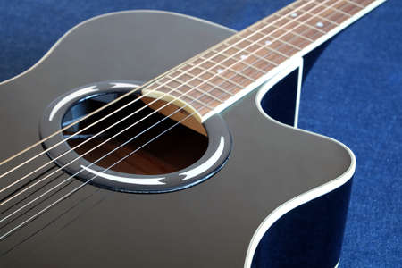 Classic semi-acoustic six strings guitar black color top with cutaway fragment on blue background diagonal view close up Banco de Imagens