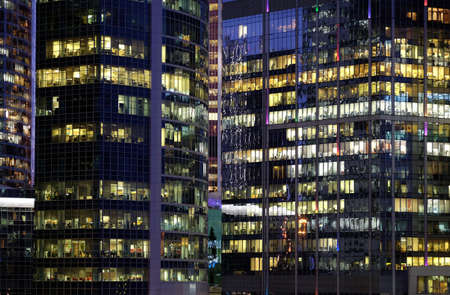 Glass walls of modern office buildings with many large panoramic windows in business cluster with working people front view at night
