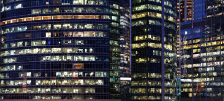 Glass walls of modern office buildings with many large panoramic windows in downtown business cluster with working people panoramic front view at night