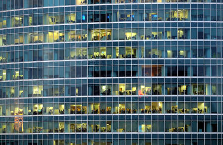 Facade of modern skyscraper building with working people in many lighted panoramic windows in the evening