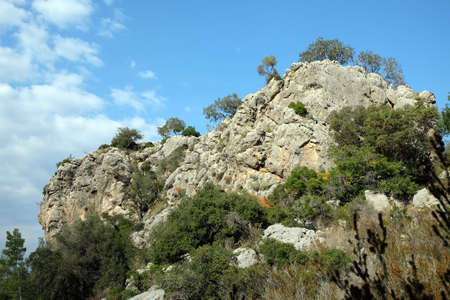 Cliff in the mountains with poor vegetation before blue sky with white clouds on bright sunny day Banco de Imagens
