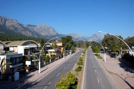 Ataturk Boulevard in Kemer and Taurus mountains at far on a bright sunny day