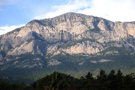 Landscape with high impregnable mountains with rocky vegetation on the slopes under blue cloudless sky on bright sunny day front view horizontal