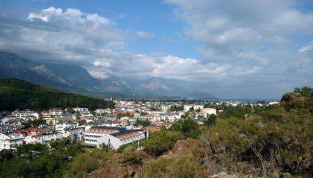 Panoramic view from observing place point to valley with Kemer city in Antalya region surrounded by high mountains and calm blue Mediterranean sea on bright sunny day Stok Fotoğraf - 142627050