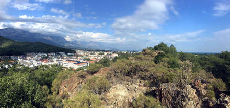 Wide panoramic view from observing place point to valley with Kemer city in Antalya region surrounded by high mountains and calm blue Mediterranean sea on bright sunny day