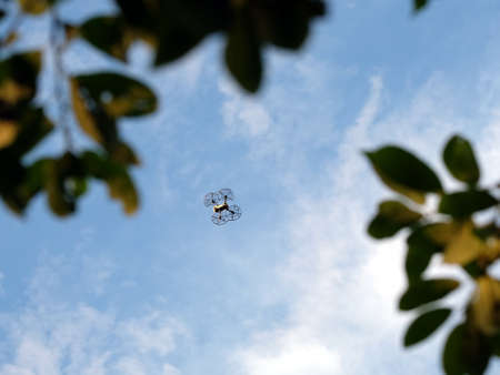 Four engine drone with engine protection grid flying high in the blue sky with calm white clouds view from tree branches Stock fotó