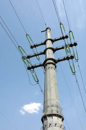 High-voltage strong power line metal prop painted gray with many wires on electrical insulation view from bottom to top close up Foto de archivo