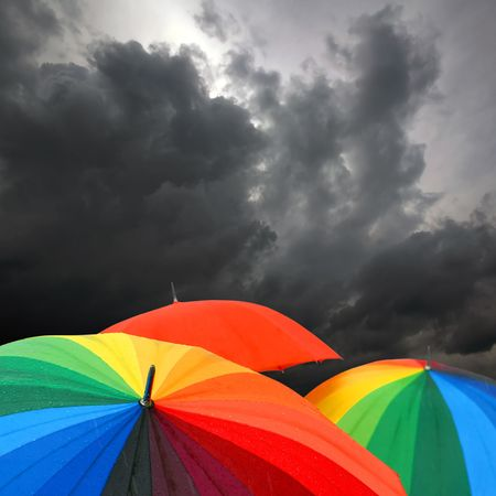 monsoon clouds: Rainbow collored umbrellas and dark cloudy sky in autumn time
