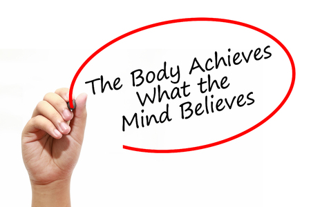 believes: Man Hand writing The Body Achieves What the Mind Believes with marker on transparent wipe board. Business, internet, technology concept. Stock Photo