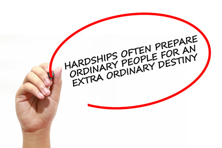 hardships: Man writing HARDSHIPS OFTEN PREPARE ORDINARY PEOPLE FOR AN EXTRA ORDINARY DESTINY with marker on transparent wipe board.