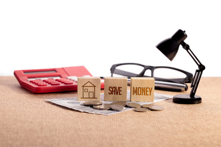 save heating costs: Save Money with wooden block on cash money with calculator, pen, glasses and desk lamp - Real Estate Concept - House with text on wooden block