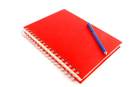 planner with red cover and blue pen over white background Stock Photo