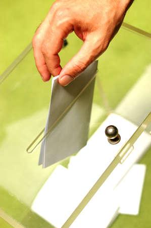 ballot: Hand putting a blank ballot inside the box, elections concept