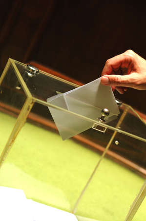 Hand putting a blank ballot inside the box, elections concept