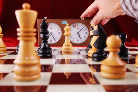 ajedrez: De ajedrez de madera y la mano que se inicia un reloj de ajedrez Foto de archivo