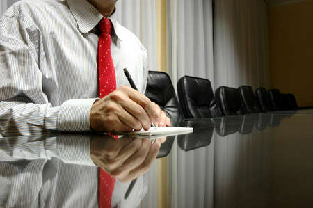 Business manager writing on blank paper in board room, business concept Stock Photo