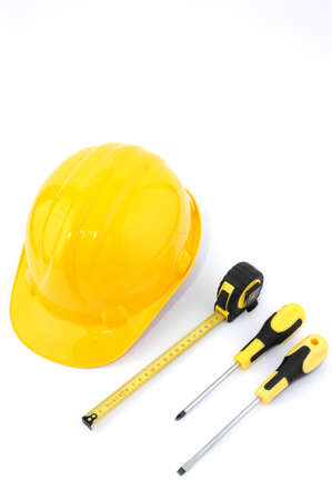 Safety helmet, measuring tape and screwdriver isolated on white photo
