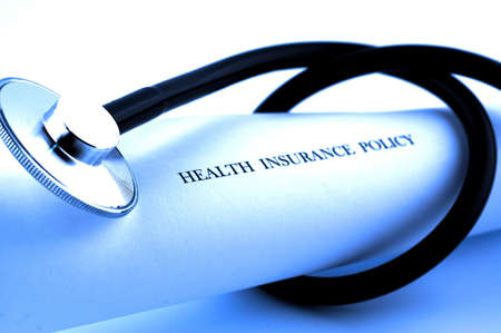 Stethoscope wrapped around health insurance policies, SOFT FOCUS photo