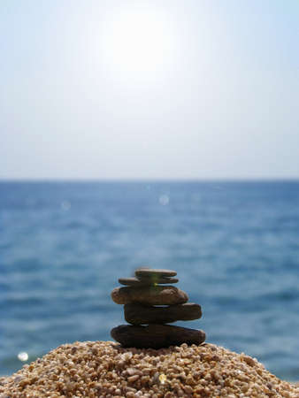 massage symbol: spa stones on the beach, sea and blue sky background Stock Photo