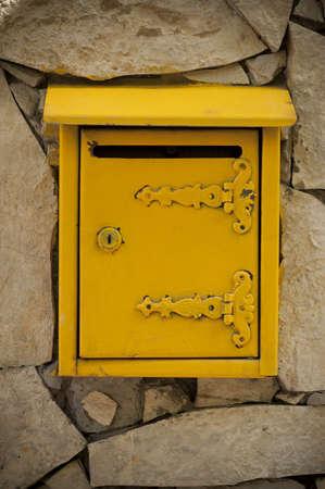 Yellow mailbox on the stone wall, Serbian model