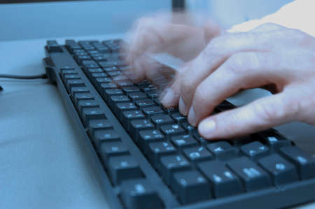 computer room in press office, hand of journalist typing on keyboards, blue tone Stock Photo