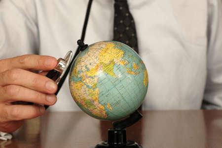 tolerancia: Doctor en mantener un estetoscopio sobre un globo, símbolo del deseo de sanar la Tierra