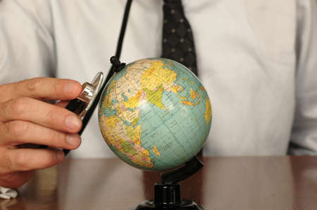tolerance: Doctor keeping a stethoscope on a globe, symbol of the desire to heal the Earth