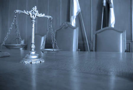 Symbol of law and justice on the table, law and justice concept, focus on the scales, blue tone photo