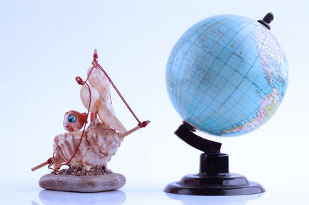 Model of sailboat made of shells and globe, travel concept