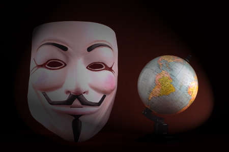 shot of an Anonymous face mask on the red background with globe, known as Guy Fawkes Mask from the movie V for Vendetta. Concept of anti-global movement