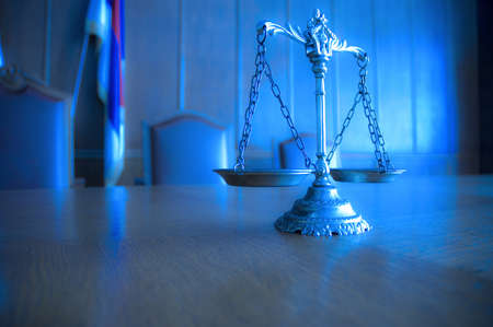 Symbol of law and justice in the empty courtroom, law and justice concept, focus on the scales, blue tone photo