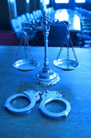 Symbol of law and justice with handcuffs in the empty courtroom, focus on the scales, blue tone