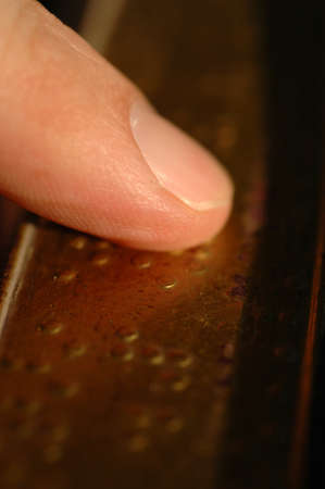Macro of fingertips reading Braille code for the blind from a textbook