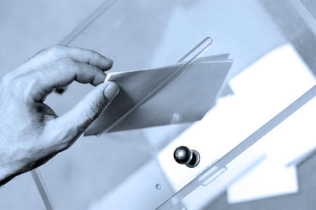 elections: Hand putting a blank ballot inside the box, elections concept, Blue tone Stock Photo