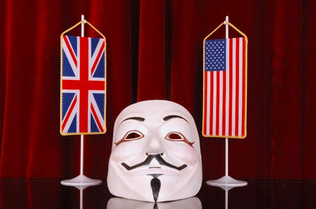 shaken: BELGRADE, SERBIA – AUGUST 1, 2014: Mask as a symbol of hacktivist groups presents collection and distribution of top secret data. US and GB flags presenting powers that were shaken by the hacktivist groups, and red background present global political stag