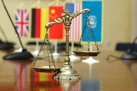 law: Decorative Scales of Justice with blurred National flag of different countries, concept of International Law and Order