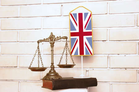 Decorative Scales of Justice, book and British flag with white wall background Stock Photo