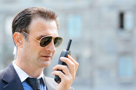 seguridad en el trabajo: Servicio de seguridad con gafas y walkie-talkie en la mano, foco suave
