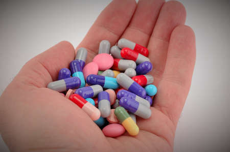 doctor holding pills: Hand holding multicolored pills, health care concept