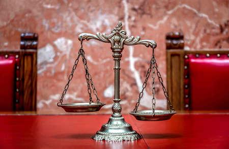 justiz: Symbol von Recht und Gerechtigkeit auf dem roten Tisch, Recht und Gerechtigkeit Konzept, den Schwerpunkt auf die Waage