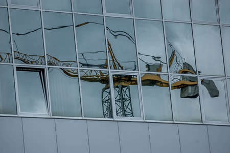 crane reflected in the windows of an office building