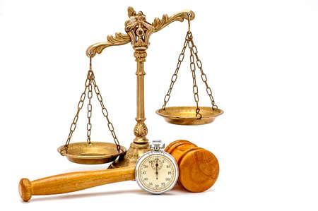 ley: Cronómetro de plata viejo, martillo de madera y escalas decorativas de la justicia en el fondo blanco, se centran en el martillo y cronómetro