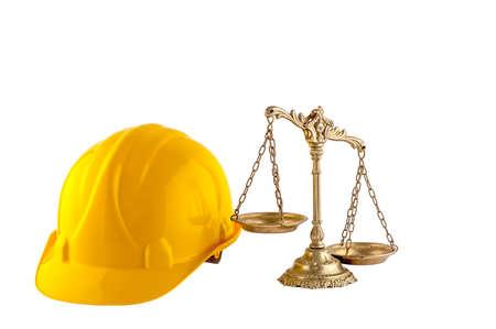 ley: balanza de la justicia y el casco amarillo aislados sobre fondo blanco, el concepto de derecho de la industria Foto de archivo