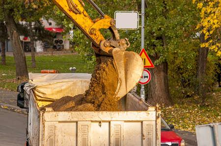 dumper truck: industrial excavator loading earth into a dumper truck