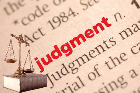 judgment: Dictionary definition of judgment and scales of justice on the book. Close-up view, with paper textures Stock Photo