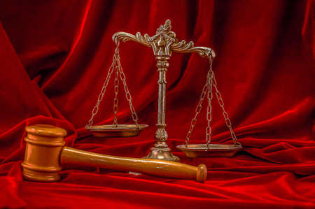 verdicts: Symbol of law and justice on the red velvet background