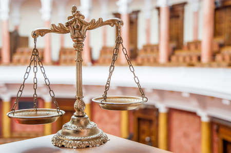 Scales of justice in the empty courtroom, law and justice concept, focus on the scales Stock Photo